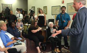 Rep. Frank Pallone (D-6), standing, addresses Norma Rodgers, New Jersey State Nurses Association president (sitting, navy shirt) during a sit-in at his New Brunswick office.